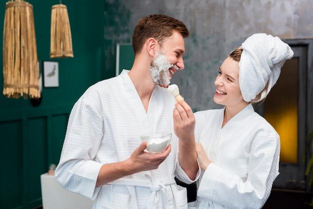 Vista lateral do casal em roupões de banho com espuma de barbear
