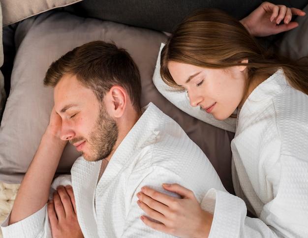 Vista lateral do casal em roupões dormindo