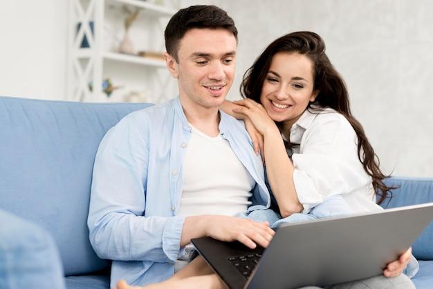 Vista lateral do casal feliz em casa com o laptop