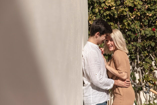 Vista lateral do casal feliz posando enquanto abraçava