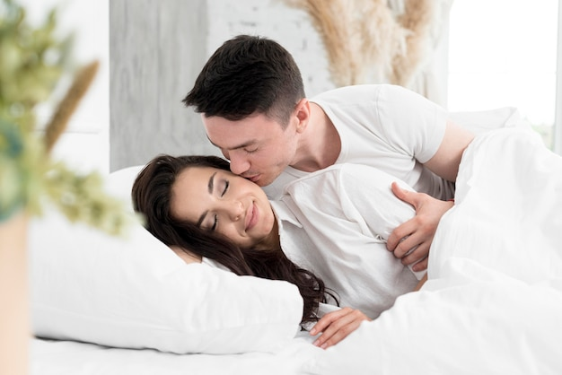 Vista lateral do casal na cama, sendo romântico