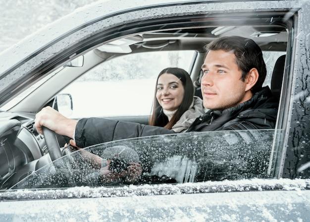 Vista lateral do casal no carro durante uma viagem