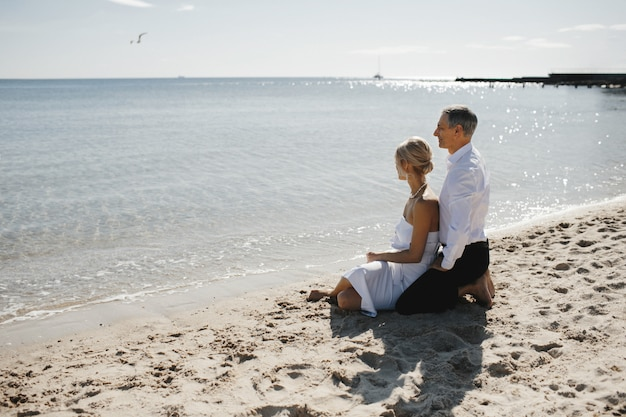 Vista lateral do casal que está sentado na praia perto do mar e olhando a paisagem de tirar o fôlego
