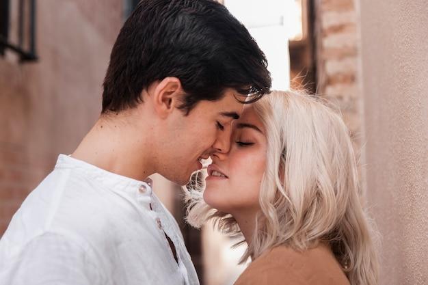 Vista lateral do casal se beijando