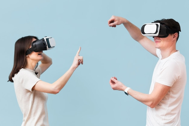 Vista lateral do casal se divertindo com fone de ouvido de realidade virtual