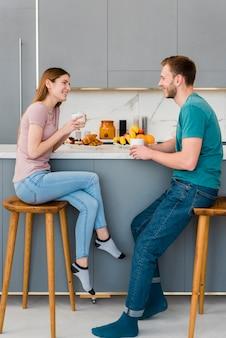 Vista lateral do casal segurando copo na cozinha