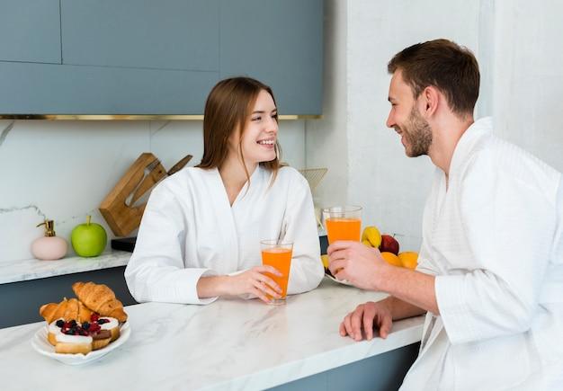 Vista lateral do casal segurando copos de suco