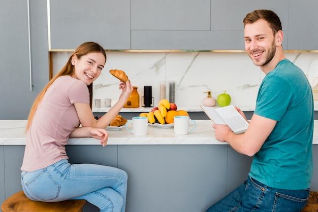 Vista lateral do casal segurando croissant e livro
