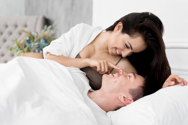 Vista lateral do casal sendo romântico na cama