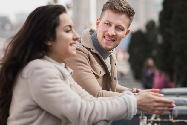 Vista lateral do casal sorridente ao ar livre
