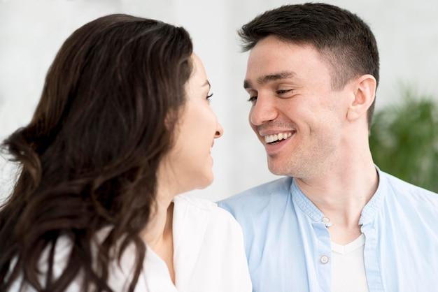 Vista lateral do casal sorridente em casa
