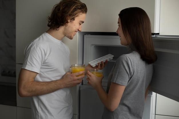 Vista lateral do casal sorridente segurando copos de suco de laranja