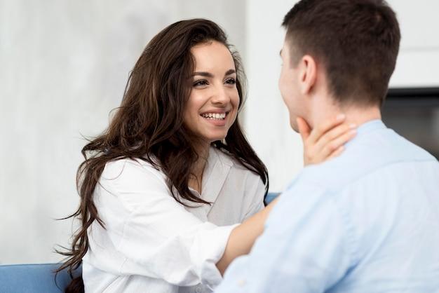 Vista lateral do casal sorrindo um para o outro