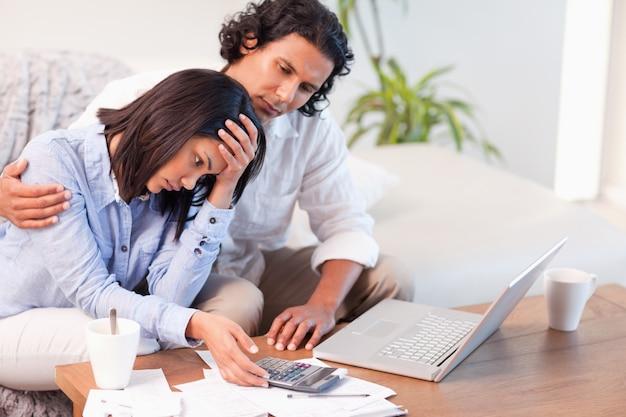 Vista lateral do casal tendo dificuldade em pagar suas contas