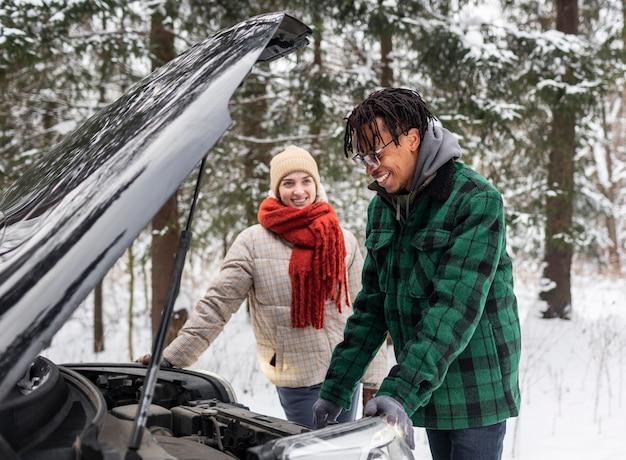 Vista lateral do casal verificando o carro