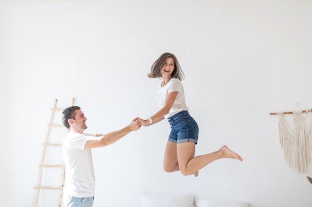 Vista lateral do casual homem sorridente, segurando as mãos de mulher despreocupada, pulando no sofá na sala moderna, com paredes brancas