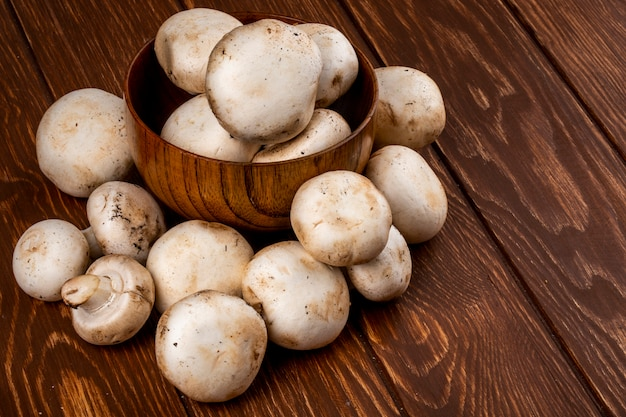 Vista lateral do champignon de cogumelos frescos em uma tigela sobre fundo rústico de madeira
