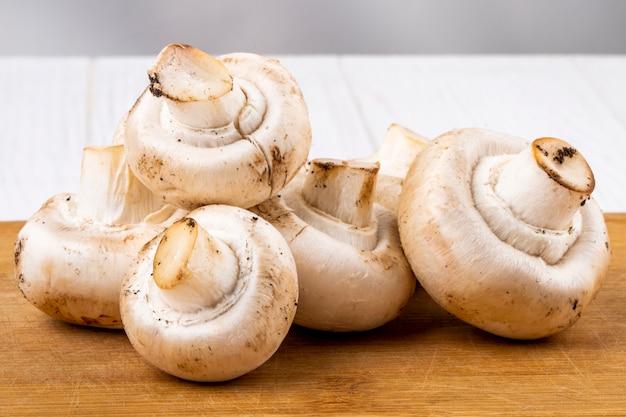 Vista lateral do champignon de cogumelos frescos na placa de madeira no fundo branco