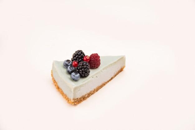 Vista lateral do cheesecake azul com frutas diferentes nele isolado sobre o branco