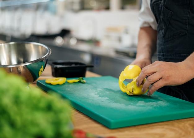 Vista lateral do chef com avental cortando pimentão