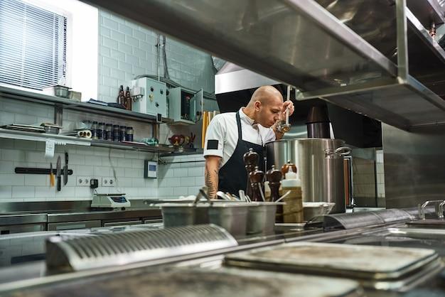 Vista lateral do chef de avental com tatuagens nos braços, sentindo o cheiro de uma sopa na cozinha de um restaurante