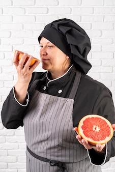 Vista lateral do chef feminino cheirando a toranja cortada