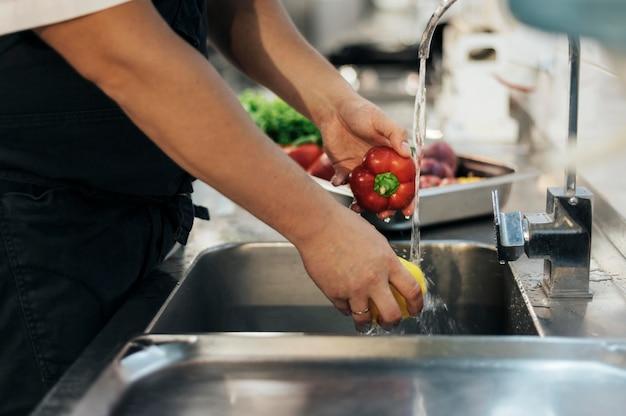 Vista lateral do chef lavando vegetais