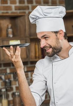 Vista lateral do chef masculino feliz segurando a sobremesa no prato