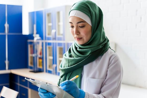 Vista lateral do cientista feminina com hijab e bloco de notas