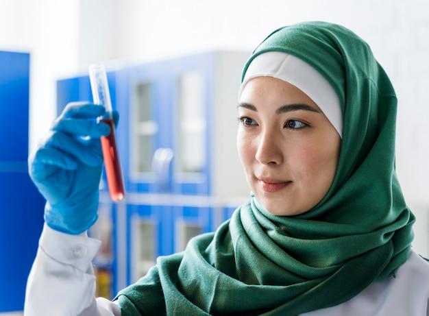 Vista lateral do cientista feminina com hijab segurando a substância