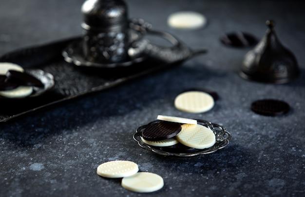 Vista lateral do círculo de bombons de chocolate em uma mesa preta jpg