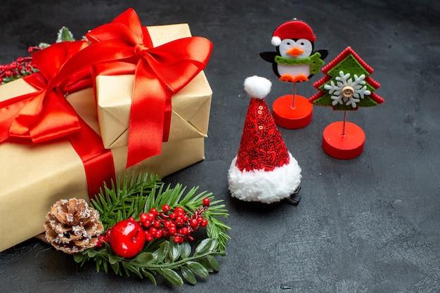 Vista lateral do clima de natal com lindos presentes com fita em forma de arco e acessórios de decoração de ramos de pinheiro chapéu de papai noel cones de coníferas em um fundo escuro