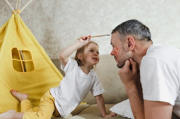 Vista lateral do close-up de uma menina feliz, aplicando o pincel no rosto do pai. um pai bonito e sorridente brinca com sua filha no sofá em casa.