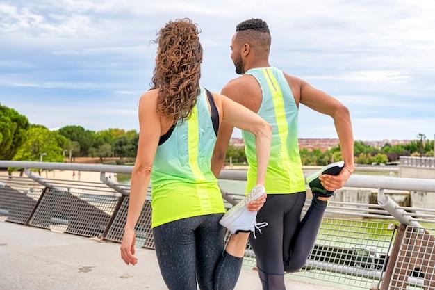 Vista lateral do close-up de uma mulher branca e um homem negro, realizando exercícios de alongamento nas pernas, vestida com roupas esportivas e esticando os músculos depois de correr pelo parque