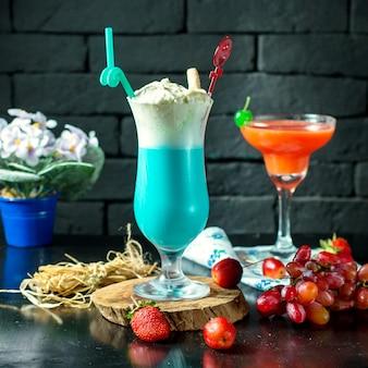 Vista lateral do cocktail azul com chantilly em um copo na mesa de madeira