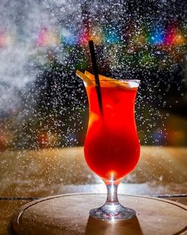 Vista lateral do cocktail cítrico com fatias de laranja e palha em um copo na mesa