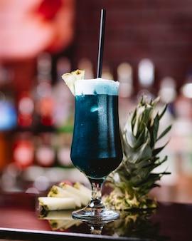 Vista lateral do cocktail de curaçao azul em um copo alto com uma fatia de abacaxi em cima da mesa