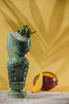 Vista lateral do cocktail exótico em um copo de tiki e manga fresca na parede amarela