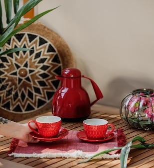 Vista lateral do conjunto de chá vermelho de xícaras e bule em uma mesa de madeira