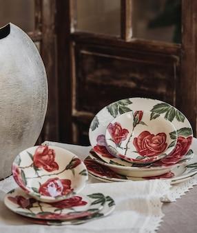 Vista lateral do conjunto de pratos estampados de flores em cima da mesa