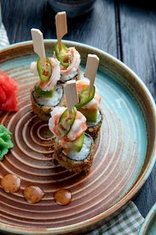 Vista lateral do conjunto de rolos de sushi assado com camarão servido com wasabi e gengibre em um prato na madeira