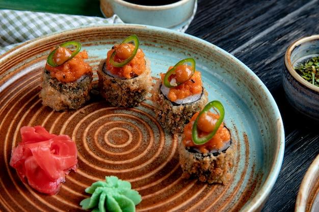 Vista lateral do conjunto de rolos de sushi assado com wasabi e gengibre em um prato