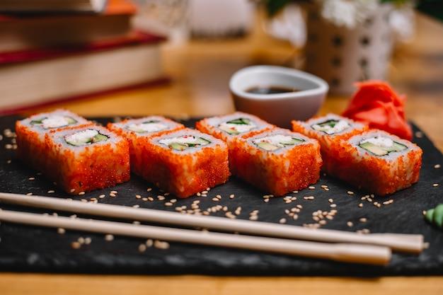 Vista lateral do conjunto de sushi rola com queijo creme de carne de caranguejo e abacate no caviar de peixe voador com molho de soja em uma placa preta