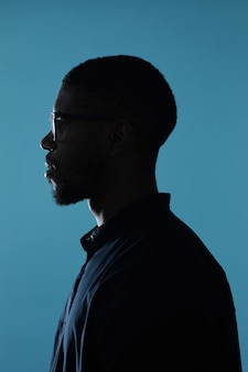 Vista lateral do contorno do perfil da silhueta masculina afro-americana contra um fundo azul profundo