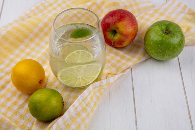Vista lateral do copo de água com lima e limão em uma toalha amarela quadriculada com maçãs em uma superfície branca