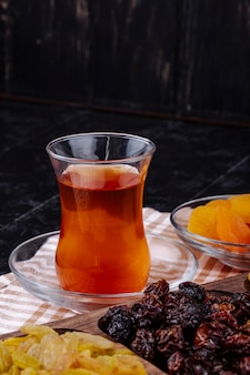 Vista lateral do copo de armudu de chá com cerejas secas e damascos secos em cima da mesa