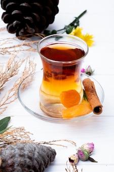 Vista lateral do copo de armudu de chá com damascos secos, pau de canela e botões de rosa secos espalhados em branco