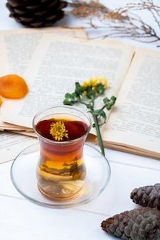 Vista lateral do copo de armudu de chá com paus de canela, dentes de leão e pinhas com um livro aberto sobre a mesa