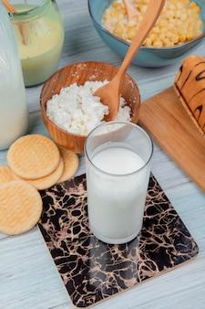 Vista lateral do copo de leite com biscoitos, leite condensado, queijo cottage, rolo de cereais na mesa de madeira