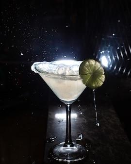 Vista lateral do copo de martini com fatia de limão no preto